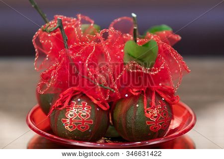 Tangerine Fruits In Tray Wrapped In Red Clothes, With Chinese Character Stickers Meaning Double Happ