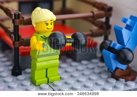 Tambov, Russian Federation - January 21, 2020 Lego Woman Minifigure Lifting Weights In A Gym.