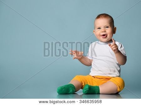Frolic Infant Child Baby Boy Kid In Yellow Pants And White T-shirt Is Sitting On The Floor Stick His