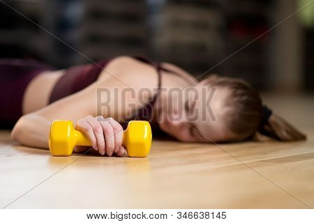Dumbbell In The Hand Of A Girl Who Is Resting Lying On The Floor In The Gym, Selective Focus