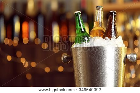 Beer In Metal Bucket With Ice Against Blurred Lights, Closeup. Space For Text