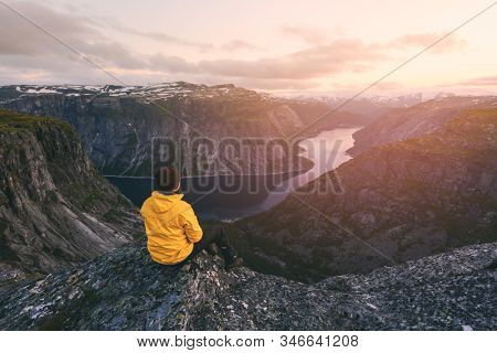 Alone tourist on Trolltunga rock - most spectacular and famous scenic cliff in Norway. Landscape photography