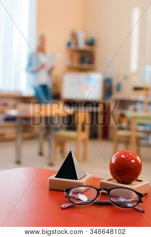 Selective Focus Of Educational Game And Eyeglasses On Desk With Teacher At Background In Montessori