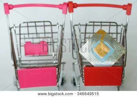 Two Red Supermarket Trolleys, One Of Which Contains An Rfid Tag. Shoplifting Prevention. Goods Secur
