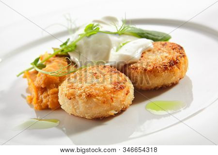 Halibut cutlets or fish cakes with cream cheese on white restaurant plate isolated. Homemade golden fried seafood meatballs, breaded flatfish fillet in breadcrumbs with white sauce and herbs closeup