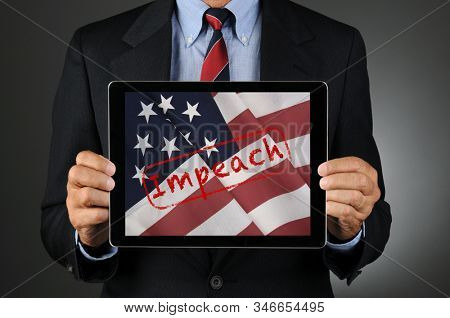 Politician Holding Tablet with American Flag and the Word Impeach. Man is  unrecognizable.