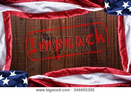 Top view of an American flags on a dark wood table forming a frame with the word Impeach in the middle.