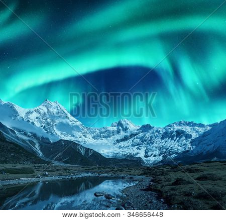 Aurora Borealis Over The Snowy Mountains, Coast Of The Lake And Reflection In Water. Northern Lights