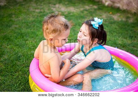 Two Little Brother And Sister Playing And Splashing In Pool On Hot Summer Day. Children Swimming In