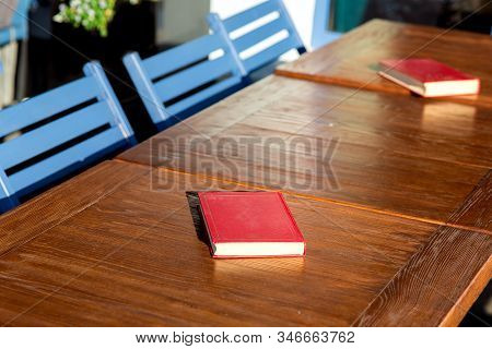 Untitled Red Hardcover Book On A Wooden Brown Table With Blue Chairs Lit By The Sunlight Of A Empty