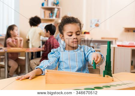 Selective Focus Of Kid Playing Educational Game At Table With Children At Background In Montessori S