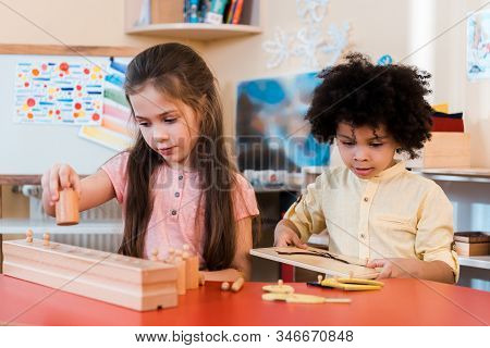 Selective Focus Of Children Playing Wooden Games During Lesson In Montessori School