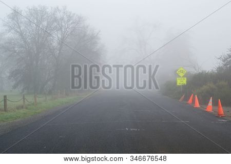 A Paved Road On A Foggy Winters Day,  Visibility Is Low And The Way Ahead Is Unclear- Dangerous Driv