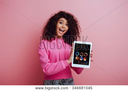 Excited Bi-racial Girl Showing Digital Tablet With Graphs And Charts On Pink Background