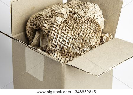 A Close-up Shot Of An Open Generic Brown Carton Packaging Box With Brown Cross-cut Paper Filling.