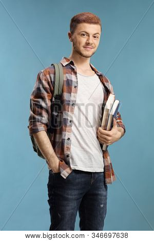 Male student with books and backpack isolated over blue background