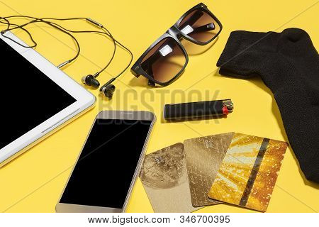 Tablet Pc, Smartphone Earphones, Cigarette Lighter, Sock, Sunglasses And A Gold Bank Card Lying On A