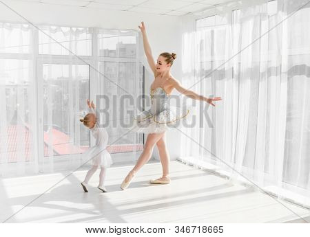 Young gorgeous ballerina with her little daughter dancing in studio. Happy ballerina with her child girl standing on tiptoes. Mother and daughter dancing ballet