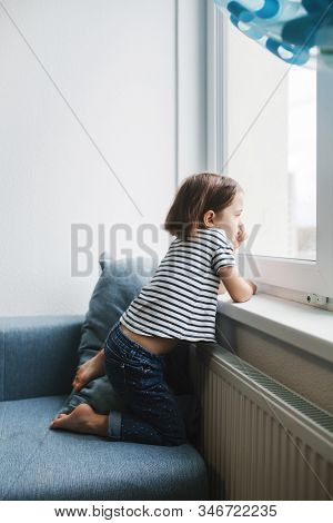 Little Bored Girl Sitting On The Couch At Home And Looking At The Window. Full Lenght Portrait With