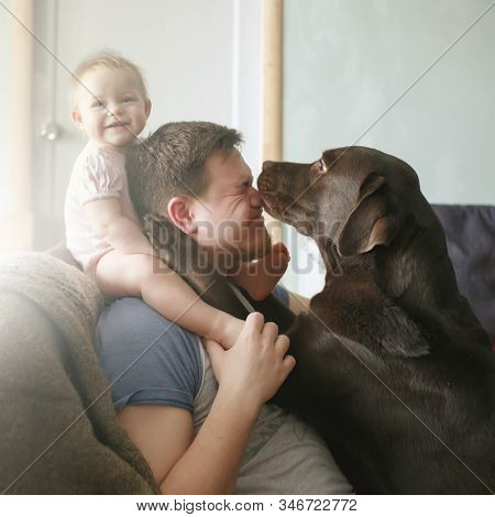 Family Portrait Of Young Caucasian Father With Cute Smiling Little Baby Girl Sitting On His Shoulder