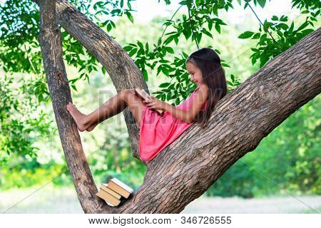 Charming little girl with long brown hair reads book outdoor sitting on tree in summer park or in a forest glade. Child booklover. Education, reading, kid's leisure