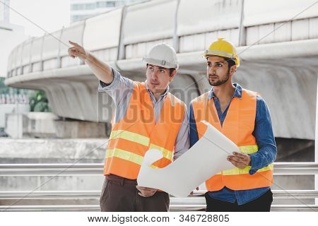 Engineer Boss And Foreman Or Worker Working Together At Worksite In City. Employer Guy Pointing Fing