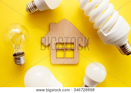 Led Lamp, Fluorescent And Incandescent With Wooden House On A Yellow Background. Top View, Flat Lay.
