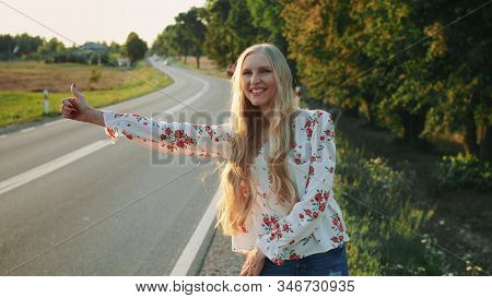 Young Woman Hitchhiking On Countryside Road. Young Female With Red Suitcase Standing On Roadside And