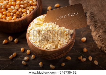 Corn flour  in a wooden bowl isilated on a wooden background