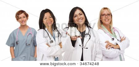 Attractive Hispanic Female Doctor or Nurse Holding Out Baby Shoes and Support Staff Behind Isolated on a White Background.