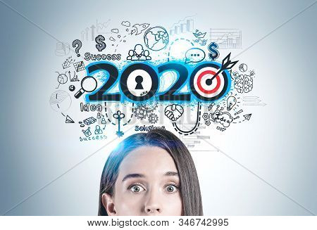 Astonished Young Woman Standing Near Gray Wall With Colorful 2020 Goals Sketch. Concept Of Developme