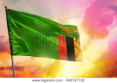 Fluttering Zambia Flag On Beautiful Colorful Sunset Or Sunrise Background. Zambia Success And Happin