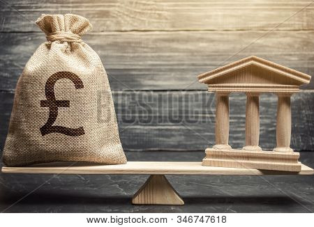 Money Bag And Government Building On The Scales. Business And Finance Concept. Deposit, Loan And Inv
