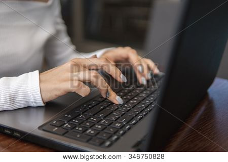 Beautiful Young Woman In White T-shirt Is Working On Laptop And Smiling While Sitting Outdoors In Ca