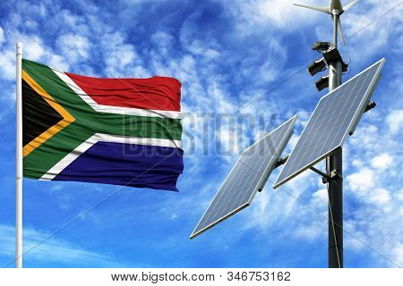 Solar Panels On A Background Of Blue Sky With A Flagpole And The Flag Of South Africa