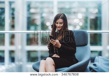 A Charming Mature Woman Entrepreneur On An Armchair Of A Classic Blue Color Using A Smartphone; A Da