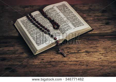 Open Holy Bible And Beads Crucifix On A Old Oak Wooden Table. Beautiful Red Wall Background.