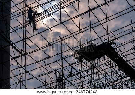 Silhouette Of Workers High On Scaffolding In A Construction Site, With Hard Hats, But No Other Safet