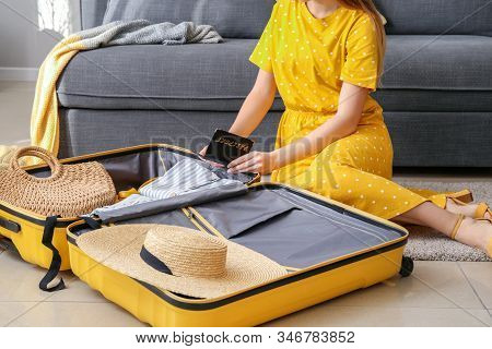 Young Woman Packing Luggage At A Home