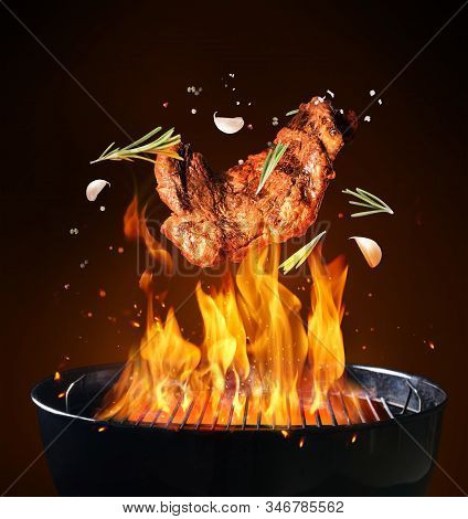 Falling Tasty Meat With Spices On Barbecue Grill With Flame Against Dark Background