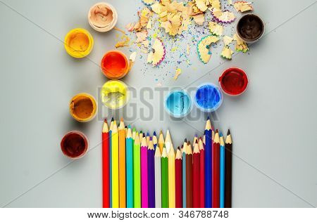 Multicolored Sharpened Pencils And Jars With Paint On A Gray Background