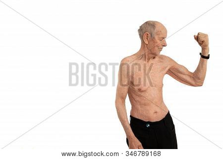 Waist Up Portrait Of An Old Man With White Hair Stands Naked Showes His Biceps And Looking At It, Is