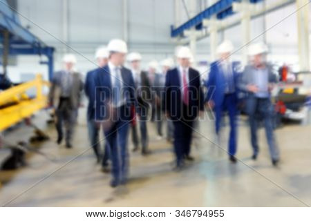 Unrecognizable people visits industrial enterprise. Motion blur, defocused image.
