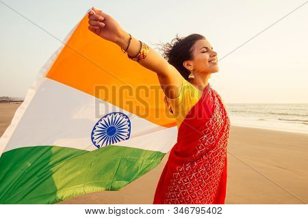 Beautuful Woman Holding Indian Flag Tricolour , Wearing Red Tradition Sari On Sea Beach In Goa