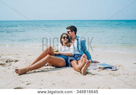 Happy Young Romantic Couple In Love Sitting And Kissing On The Beach. Young Couple In Honeymoon Havi