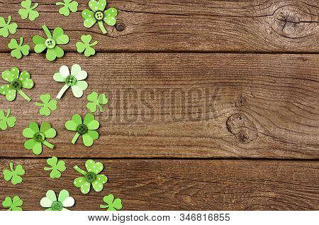 St Patricks Day Side Border Of Handmade Paper Button Shamrocks. Top View Over A Rustic Wood Backgrou