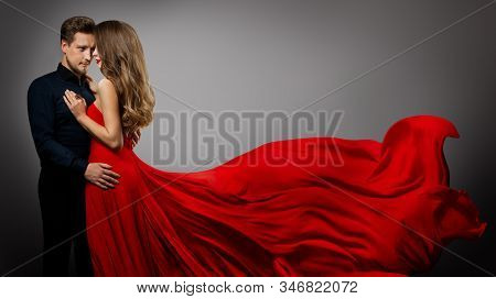 Beautiful Couple, Fashion Woman In Red Silk Dress And Elegant Man Studio Portrait, Gown Fluttering O