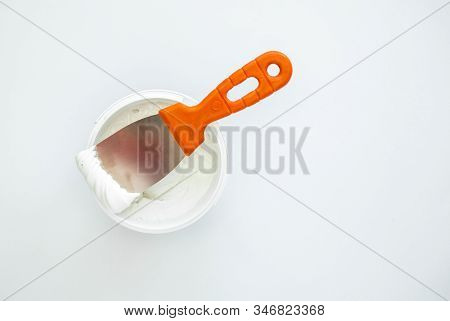 Filler Putty In The Bucket, White Plaster And Spatula. Repair Construction Stucco Design Concept