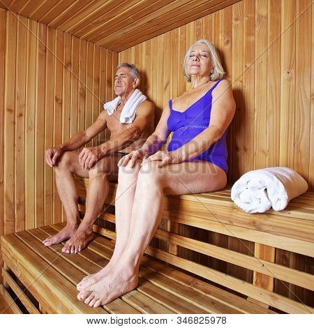 Couple of seniors sweating together in the sauna in the hotel