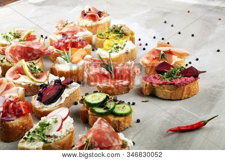 Assorted Bruschetta With Various Toppings. Appetizing Bruschetta Or Brie Crostini. Variety Of Small